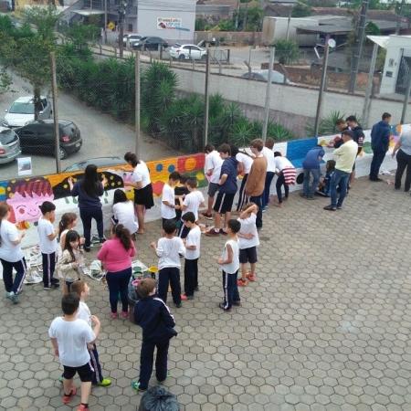 Cooperação entre alunos para colorir com arte o muro da Escola Albano Kan...